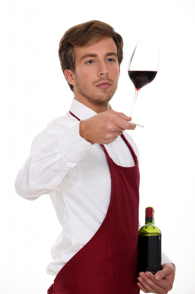 Sommelier holding up a glass of wine
