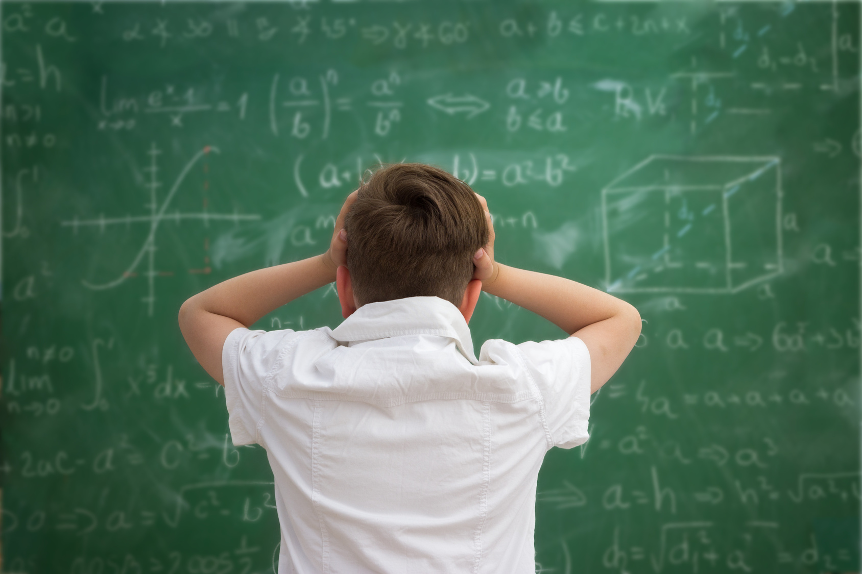 Schoolboy holding hands on his head, getting crazy and looks at the blackboard with formulas
