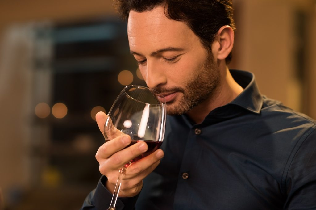 Man smelling red wine